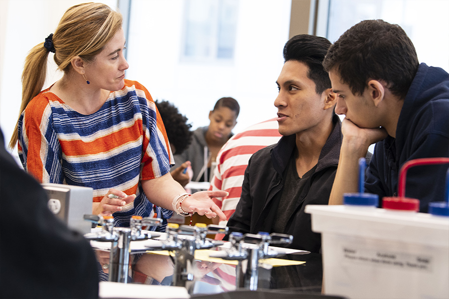 Three students interact in a biology lab course